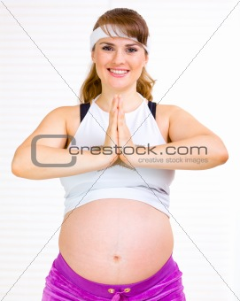 Smiling beautiful pregnant woman doing yoga exercises at home