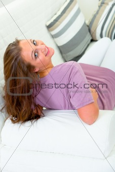 Smiling attractive young woman sitting on white sofa