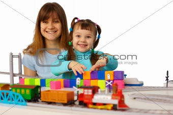 Young mother and daughter playing with toys