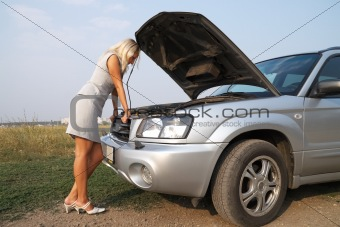 blonde looks blankly under the hood of the broken car