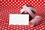 Red apple and measuring tape on a red background and card