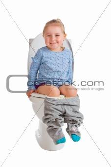 little girl is sitting on toilet