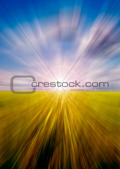 Abstract motion blurred meadow and sky with sun