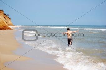 Boy running by beach
