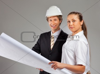 An architect wearing a hard hat and co-worker
