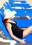 Mid age tourist woman sun tanning blue hammock row