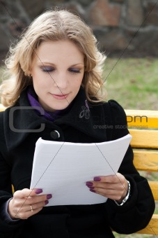 Business young woman looks in the paper