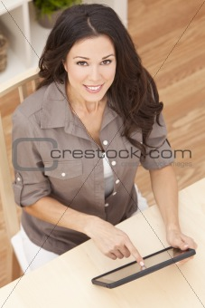 Happy Beautiful Young Woman Using Tablet Computer at Home