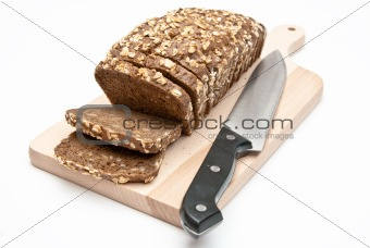sliced wholemeal bread on kitchen board and knife