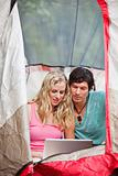 Couple working on laptop while camping
