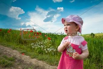 Baby-girl on a lane amongst a field
