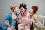Three ladies in historical dresses gossiping