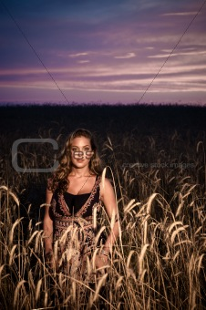 Attractive young lady in a field of wheat
