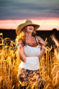 Attractive young lady in a straw hat laughing hard