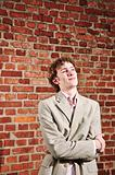 A young businessman standing against a brick wall