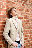 A young businessman against a brick wall, relaxed stance