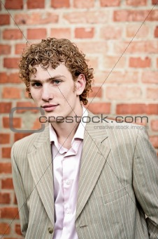 Close portrait of a young businessman against a brick wall