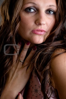 Attractive  girl with long brown hair holding her hand near neck