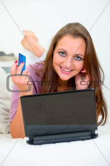 Smiling pretty woman lying on sofa and using credit card to shop from net