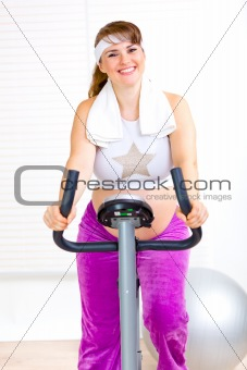 Smiling beautiful pregnant woman working out on static bike