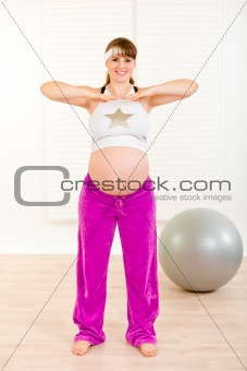 Smiling beautiful pregnant female doing exercise at home