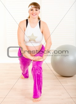 Smiling beautiful pregnant woman doing stretching exercises at home