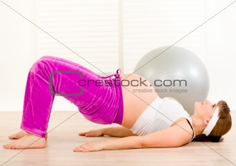 Beautiful pregnant female doing fitness exercises at  home