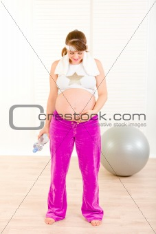 Pregnant woman in sportswear holding bottle of water and looking on belly