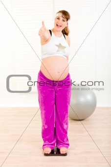 Pleased beautiful pregnant woman standing on weight scale and showing thumbs up gesture