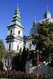 White church with green domes and flowerbeds in the town