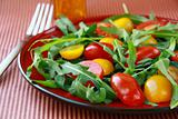 salad with arugula and cherry tomatoes on a striped background
