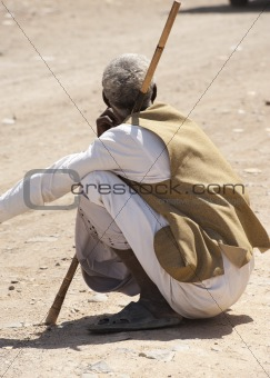 Local bedouin man sitting in road
