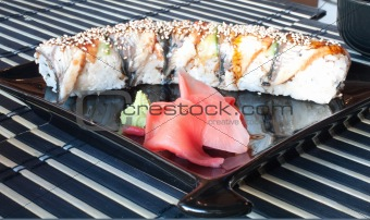 Assorted sushi plate on black plate over bamboo mat