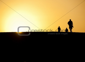 Three people silhouetted in sunset