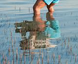 Reflection of man standing in a tropical lagoon