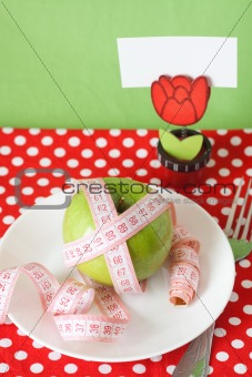 Green apple and measuring tape on a white plate and fork