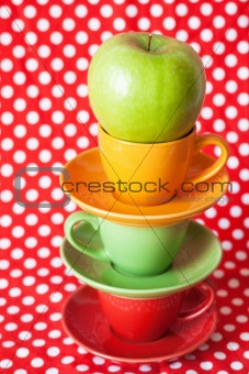 Green apple and bright cup with a red background
