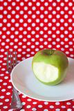 Green apple on a white plate on a red background