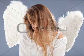 beautiful blonde angel against grey  background