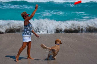 Senior Woman Playing with Dog on a Florida Beach.