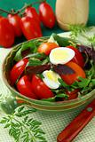 Fresh salad with tomato and quail eggs in  bowl on a green tablecloth