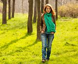 Beautiful red-haired girl walking at green grass at park. 