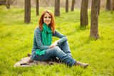 Beautiful red-haired girl sitting at green grass at park. 
