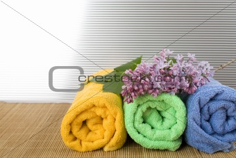 Towels folded lie next to them a branch of lilac