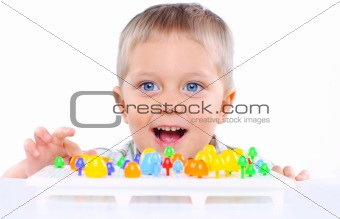 Little cute boy playing with multicolored mosaic