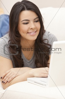Beautiful Hispanic Woman Laying on Sofa Using Laptop Computer