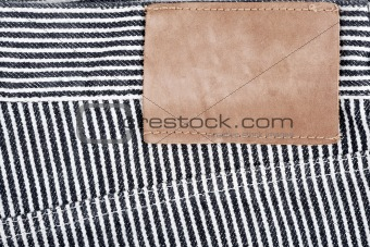 Blank leather jeans label sewed on a striped jeans
