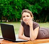Young pretty woman with laptop lying on the bench at a park