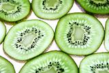Detail view of kiwi slices backlighted over white background.