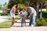 African American Family WIth Boy Riding Bike &amp; Happy Parents 